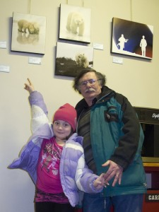 Bruce Raby and grand-daughter Oksana pointing to her favorite photo of her grand-father's exhibit at the Studio Theater in Perth.