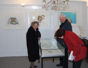 """Les visiteurs admirant la maison de poupée pour enfants, un igluvigaq et de ses habitants, tous représentés par des os de phoque. L'exposition """"Trésors de l'Arctique""""  à Thayngen."""